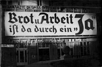 "photo: ÖNB, © VGA, ""Anschluss"" of Austria to the ""German Reich""; the photo shows a huge board to the façade of a house, 1938"